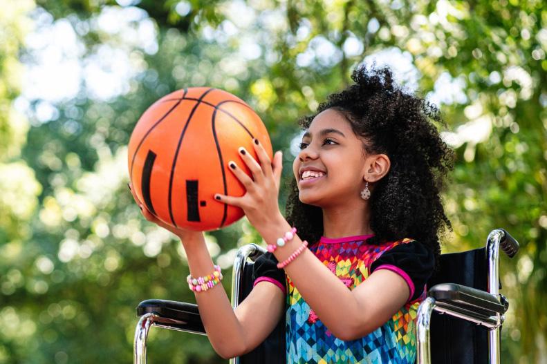 girl in wheelchair catching ball